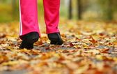 Runner legs running shoes. Woman jogging in autumn park — Stock Photo
