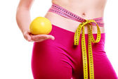 Time for diet slimming. Woman tape around body fruit in hand — Stock Photo