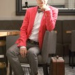 Young handsome stylish man with suitcase waits — Stock Photo