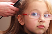 Hairdresser combing hair little girl child in hairdressing beauty salon — Stock Photo