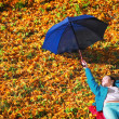 Young girl relaxing with umbrella in autumnal park — Stock Photo #39595673
