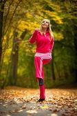 Fitness caber menina mulher loira fazendo exercício no parque outonal. esporte. — Fotografia Stock