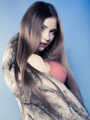 Sexy girl with long hair in red bra underwear and fur coat on blue — Stock Photo