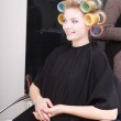 Woman in beauty salon, blond girl hair curlers rollers by hairdresser. Hairstyle. — Stock Photo