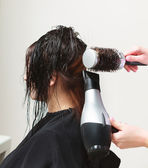 In hairdressing salon. Hairstylist with dryer drying hair of woman client. — Stock Photo