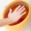 Female hand and orange paraffin wax bowl. Woman in beauty salon — Stock Photo