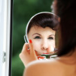 Girl applying make up reflection in mirror — Stock Photo