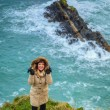 Woman standing on rock cliff by the ocean Co. Cork Ireland — Stock Photo #39939279
