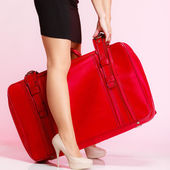 Side view woman legs with red suitcase on pink background — Stock Photo