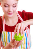 Happy housewife or chef in kitchen apron using apple timer — Stock Photo