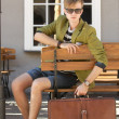 Young handsome man with suitcase waits on bench — Stock Photo
