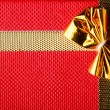 Giftbox closeup. Golden bow on red background — Stock Photo