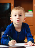 Blond boy child kid with pen writing on piece of paper. At home. — Stock Photo