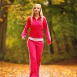 Woman running in autumn forest. Female runner training. — Stock Photo