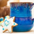 Blue mug and christmas gingerbread cake star icing decoration — Stock Photo