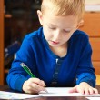 Blond boy child kid with pen writing on piece of paper. At home. — Stock Photo #40119579