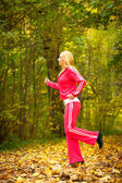 Blonde girl young woman running jogging in autumn fall forest park — Foto Stock