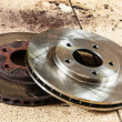 Auto in service. New and old front brake disks for modern car. — Stock Photo #40120439