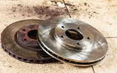 Auto in service. New and old front brake disks for modern car. — Stock Photo