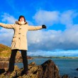 Woman standing on rock cliff at ocean, relaxing Co. Cork Ireland — Stock Photo #40324391