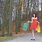 Girl in red dress with shopping bags walking in park — Stock Photo