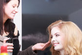 Hairstylist with hairspray and female client blond girl in salon — Stock Photo