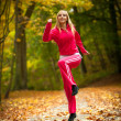 Fitness fit woman blond girl doing exercise in autumnal park. Sport. — Stock Photo