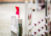 Closeup white obstacle with red flag for jumping horses. Riding competition. — Stock Photo