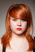 Portrait redhaired girl young woman with cherry earing on gray — Stock Photo