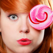 Stock Photo: Woman holding candy. Redhair girl with sweet lollipop making fun
