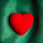 Valentine's day background. Red heart on green folds cloth — Stock Photo