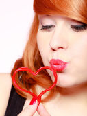 Redhaired girl holding red heart love blowing kiss. Valentines day. — Stock Photo