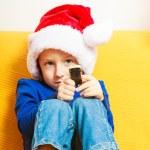 Happy childhood. Boy child kid in santa hat sitting on sofa. Christmas. — Stock Photo
