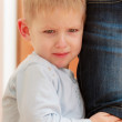 Childhood. Portrait of unhappy crying boy kid hugging leg mother. — Stock Photo #40646377