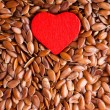 Healthy diet. Flax seeds linseed as food background and red heart — Stock fotografie