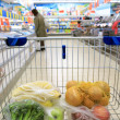 Shopping cart with grocery at supermarket — Stock Photo