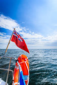 Blue sea. View from deck of yacht sailboat british flag lifebuoy. Travel. — Stock Photo