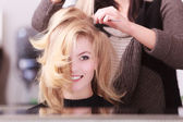 Smiling girl with blond wavy hair by hairdresser in beauty salon — Stock Photo
