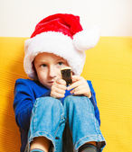 Happy childhood. Boy child kid in santa hat sitting on sofa. Christmas. — Stock Photo