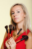 Beauty procedures, woman holds make-up brushes near face. — Stok fotoğraf