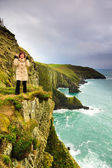 Woman standing on rock cliff by the ocean Co. Cork Ireland — 图库照片