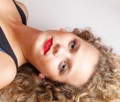 Portrait beautiful blond girl make up lying on floor studio shot — Stock Photo