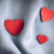Valentine's day background. Red hearts on gray folds cloth — Stock Photo #41285695