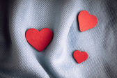 Valentine's day background. Red hearts on gray folds cloth — Stock Photo