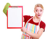 Housewife or barista in kitchen apron holds clipboard with empty blank isolated — Stock Photo