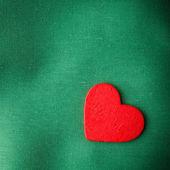 緑の布の背景に赤の木の装飾的な心. — ストック写真
