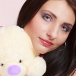 Childish young woman infantile girl in pink hugging teddy bear toy — Stock Photo #41894251