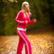Stock Photo: Blonde girl young woman running jogging in autumn fall forest park
