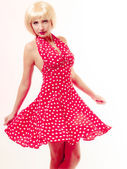Beautiful pinup girl in blond wig and retro red dress dancing. Party. — Stock Photo