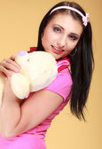 Childish young woman infantile girl in pink hugging teddy bear toy — Stock Photo